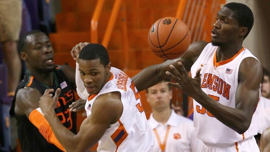 Clemson's Landry Nnoko, right, gets a rebound near teammate Jaron Blossomgame, middle, and Miami's Tonye Jekiri during the first half of of an NCAA college basketball game at Littlejohn Coliseum Tuesday, March 4, 2014, in Clemson, S.C.. (AP PHOTO/  Anderson Independent Mail, Ken Ruinard)  THE GREENVILLE NEWS OUT, SENECA NEWS OUT