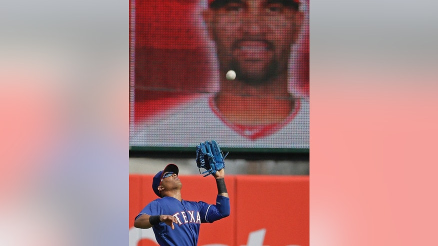 Texas Rangers' Leonys Martin catches a fly ball hit by Los Angeles Angels' Albert Pujols during the third inning of an exhibition spring training baseball game Tuesday, March 4, 2014, in Tempe, Ariz. (AP Photo/Morry Gash)