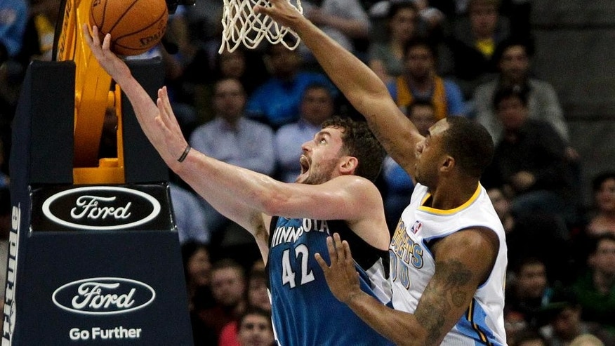 Minnesota Timberwolves' Kevin Love (42) makes layup past Denver Nuggets' Darrell Arthur (00) during the first quarter of an NBA basketball game Monday, March 3, 2014, in Denver. (AP Photo/Barry Gutierrez)