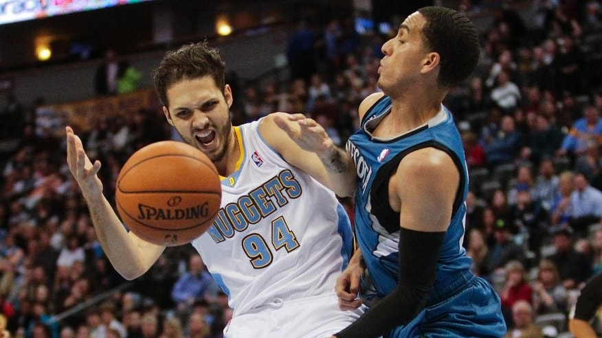 Denver Nuggets' Evan Fournier, left, is fouled by Minnesota Timberwolves' Kevin Martin, right, during the first quarter of an NBA basketball game Monday, March 3, 2014, in Denver. (AP Photo/Barry Gutierrez)
