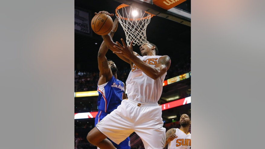 Los Angeles Clippers' DeAndre Jordan, rear, defends as Phoenix Suns' Channing Frye pulls down a rebound during the first half of an NBA basketball game, Tuesday, March 4, 2014, in Phoenix. (AP Photo/Matt York)