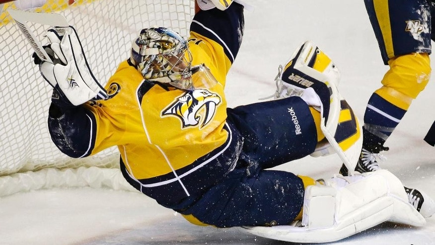 Nashville Predators goalie Pekka Rinne, of Finland, makes a stop against the Pittsburgh Penguins in the first period of an NHL hockey game Tuesday, March 4, 2014, in Nashville, Tenn. (AP Photo/Mark Humphrey)