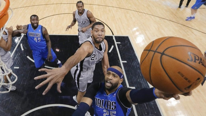 Dallas Mavericks' Vince Carter (25) drives around San Antonio Spurs' Tim Duncan (21) to score during the first half of an NBA basketball game, Sunday, March 2, 2014, in San Antonio. (AP Photo/Eric Gay)