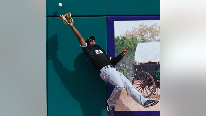 Chicago White Sox center fielder Jared Mitchell reaches but can't catch a Cleveland Indians' David Murphy fly ball that went for a one-run triple during an exhibition baseball game in Goodyear, Ariz., Tuesday, March 4, 2014. (AP Photo/Paul Sancya)