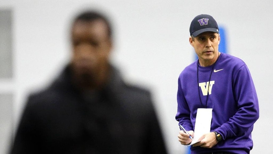 New Washington head football coach Chris Petersen, right, takes notes on the first day of spring NCAA college football practice, Tuesday, March 4, 2014, in Seattle. (AP Photo/Ted S. Warren)