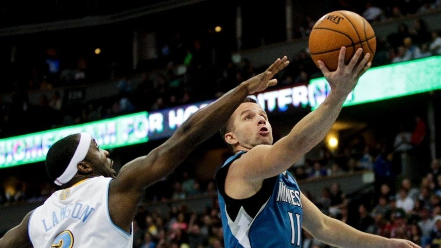 Minnesota Timberwolves'  J.J. Barea (11) makes a layup past Denver Nuggets' Ty Lawson (3) during the third quarter of an NBA basketball game Monday, March 3, 2014, in Denver. The Timberwolves won 132-128. (AP Photo/Barry Gutierrez)