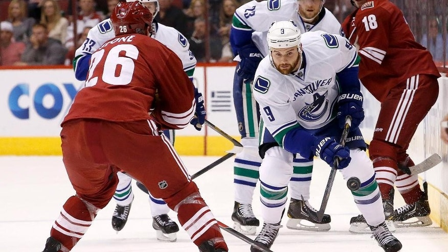 Vancouver Canucks' Zack Kassian (9) passes the puck past Phoenix Coyotes' Michael Stone (26) during the first period of an NHL hockey game on Tuesday, March 4, 2014, in Glendale, Ariz. (AP Photo/Ross D. Franklin)