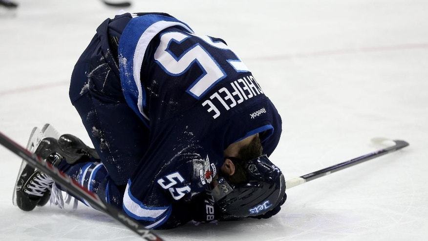 Winnipeg Jets' Mark Scheifele kneels on the ice after he was injured during the second period of an NHL hockey game against the New York Islanders in Winnipeg, Manitoba, Tuesday, March 4, 2014. (AP Photo/The Canadian Press, Trevor Hagan)