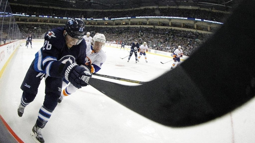 Winnipeg Jets' Blake Wheeler (26) and New York Islanders' Calvin de Haan vie for the puck during the second period of an NHL hockey game in Winnipeg, Manitoba, Tuesday, March 4, 2014. (AP Photo/The Canadian Press, Trevor Hagan)