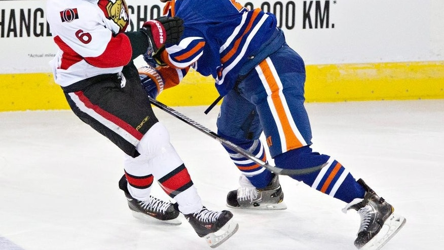Ottawa Senators' Bobby Ryan (6) is checked by Edmonton Oilers' Mark Fraser (5) during the second period of an NHL hockey game, Tuesday, March 4, 2014 in Edmonton, Alberta. (AP Photo/The Canadian Press, Jason Franson)