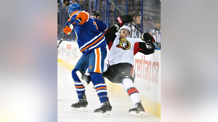 Ottawa Senators' Kyle Turris (7) is checked by Edmonton Oilers' Jeff Petry (2) during the first period of an NHL hockey game, Tuesday, March 4, 2014 in Edmonton, Alberta. (AP Photo/The Canadian Press, Jason Franson)