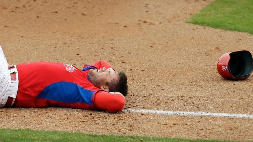 Philadelphia Phillies' Darin Ruf lays on the field after getting injured while advancing to third base on a hit by teammate Kevin Frandsen during the fourth inning of an exhibition baseball game Wednesday, March 5, 2014, in Clearwater, Fla. (AP Photo/Charlie Neibergall)