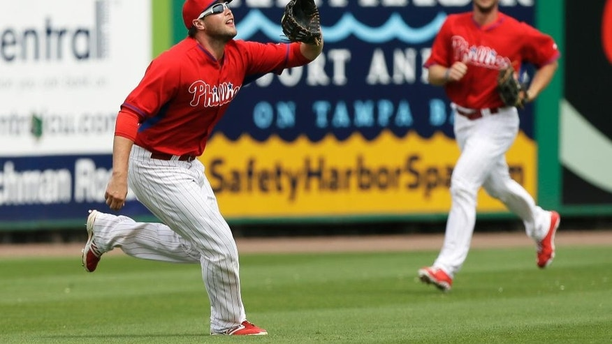 Philadelphia Phillies right fielder Darin Ruf, left, catches a fly ball hit by Atlanta Braves' Jordan Schafer during the first inning of an exhibition baseball game Wednesday, March 5, 2014, in Clearwater, Fla. Phillies right fielder Clete Thomas is at right. (AP Photo/Charlie Neibergall)