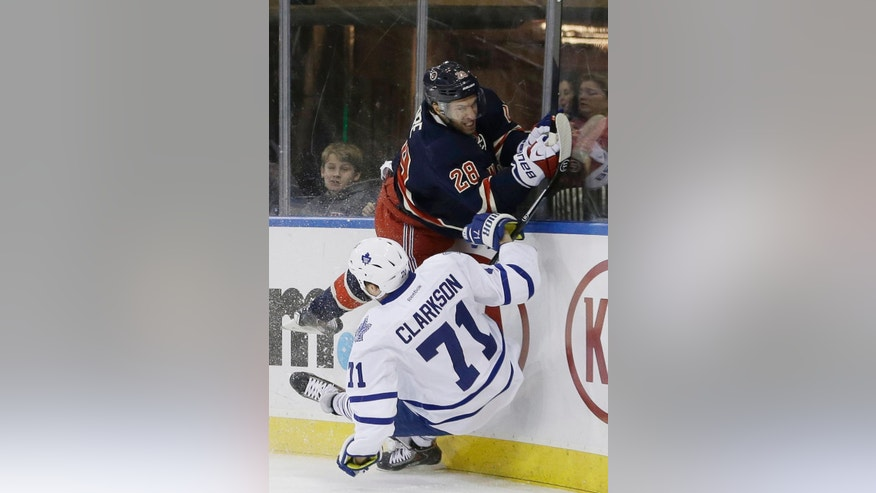 New York Rangers' Dominic Moore (28) checks Toronto Maple Leafs' David Clarkson (71) during the first period of an NHL hockey game Wednesday, March 5, 2014, in New York.  (AP Photo/Frank Franklin II)