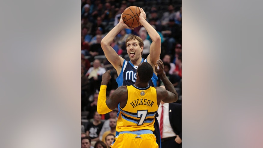 Dallas Mavericks forward Dirk Nowitzki (41) holds the ball away from Denver Nuggets center J.J. Hickson (7) in the second quarter of an NBA game in Denver on Wednesday, March 5, 2014.(AP Photo/Joe Mahoney)