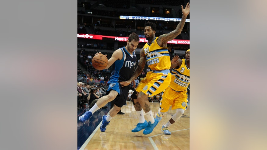 Dallas Mavericks point guard Jose Calderon (8) tiptoes along the sideline against Denver Nuggets forward Wilson Chandler (21) and Nuggets point guard Ty Lawson (3) in the second quarter of an NBA game in Denver on Wednesday, March 5, 2014.(AP Photo/Joe Mahoney)