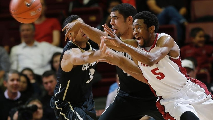 Stanford guard Chasson Randle (5) passes as Colorado forward Josh Scott, center, and guard Xavier Talton (3) defend during the first half of an NCAA college basketball game Wednesday, March 5, 2014, in Stanford, Calif. (AP Photo/Marcio Jose Sanchez)