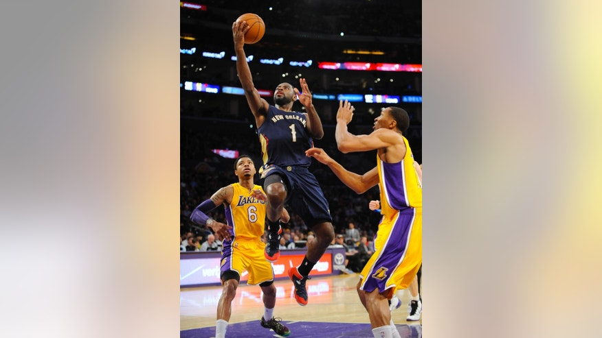 New Orleans Pelicans forward Tyreke Evans (1) gets by Los Angeles Lakers forward Wesley Johnson, right, and guard Kent Bazemore (6) as he drives to the basket during the first half of an NBA basketball game, Tuesday, March 4, 2014, in Los Angeles.(AP Photo/Gus Ruelas)