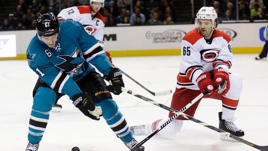 San Jose Sharks' Justin Braun (61) battles against Carolina Hurricanes defenseman Ron Hainsey (65) during the first period of an NHL hockey game on Tuesday, March 4, 2014, in San Jose, Calif. (AP Photo/Marcio Jose Sanchez)