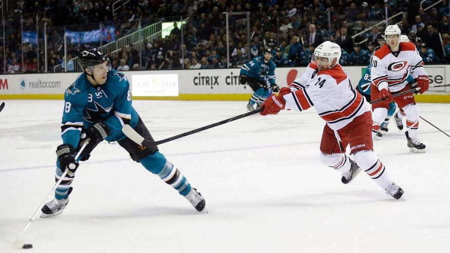 San Jose Sharks' Joe Pavelski (8) looks to shot as Carolina Hurricanes' Nathan Gerbe (14) defends during the first period of an NHL hockey game on Tuesday, March 4, 2014, in San Jose, Calif. (AP Photo/Marcio Jose Sanchez)
