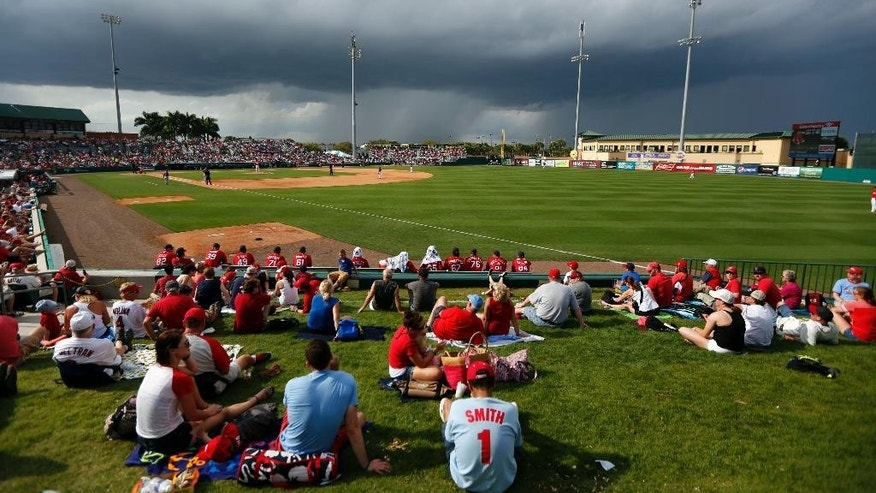 Storm clouds move in as fans watch an exhibition spring training baseball game between the St. Louis Cardinals and the Boston Red Sox at Roger Dean Stadium Wednesday, March 5, 2014, in Jupiter, Fla. (AP Photo/Jeff Roberson)