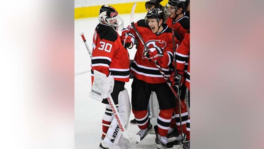 New Jersey Devils' Damien Brunner, right, celebrates with goaltender Martin Brodeur after the Devils defeated the Detroit Red Wings, 4-3, in an NHL hockey game Tuesday, March 4, 2014, in Newark, N.J. (AP Photo/Bill Kostroun)
