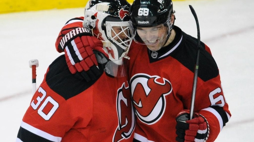 New Jersey Devils' Jaromir Jagr, right, of the Czech Republic, celebrates with goaltender Martin Brodeur after the Devils defeated the Detroit Red Wings, 4-3, in an NHL hockey game Tuesday, March 4, 2014, in Newark, N.J. (AP Photo/Bill Kostroun)