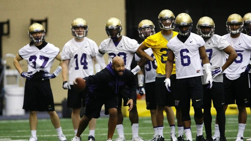 Washington defensive backs coach Jimmy Lake takes his players through a drill on the first day of spring NCAA college football practice, Tuesday, March 4, 2014 in Seattle. (AP Photo/Ted S. Warren)
