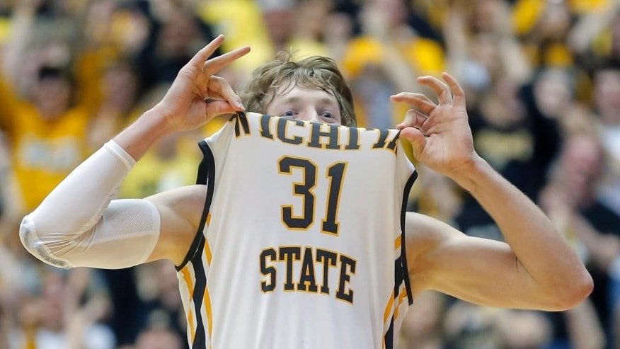 Wichita State's Ron Baker holds up his jersey at the end of the Shockers' game against Missouri State, which wrapped up a perfect 31-0 regular season on Saturday, March 1, 2014 in Wichita, Kan. (AP Photo/The Wichita Eagle, Travis Heying) LOCAL TV OUT; MAGS OUT; LOCAL RADIO OUT; LOCAL INTERNET OUT