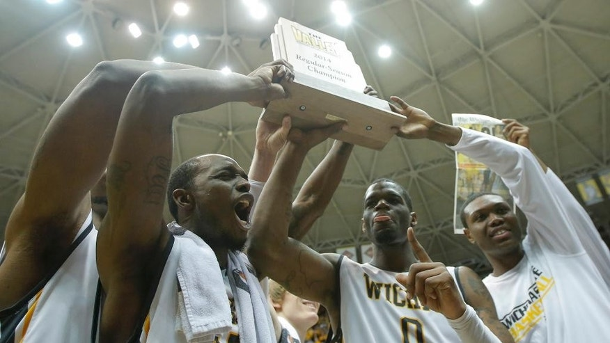 Wichita State players, from left: Nick Wiggins (15), Chadrack Lufile (0) and Cleanthony Early, right, hold up the Missouri Valley Conference regular season trophy after beating Missouri State 68-45 in an NCAA college basketball game in Wichita, Kan., Saturday, March 1, 2014.  (AP Photo/The Wichita Eagle, Travis Heying) LCOAL TV OUT; MAGS OUT; LOCAL RADIO OUT; LOCAL INTERNET OUT