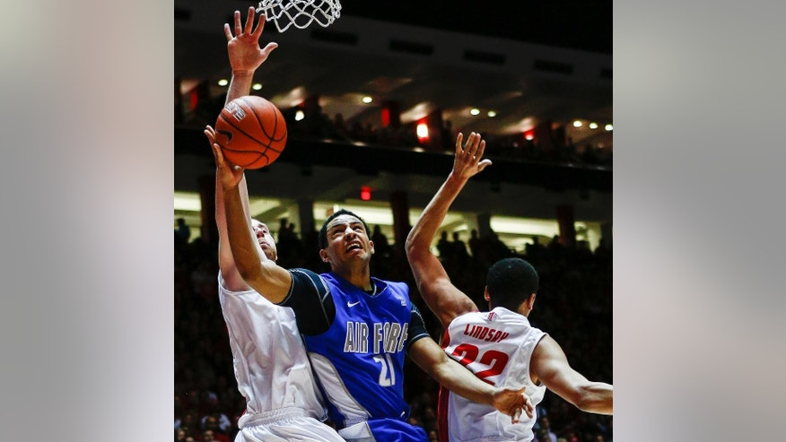 Air Force's DeLovell Earls (21) powers his way to a basket during the first half guarded by New Mexico's Alex Kirk (53) and Merv Lindsay (22) of an NCAA college basketball game at The Pit in Albuquerque, N.M., Wednesday, March 5, 2014. (AP Photo/Juan Antonio Labreche)