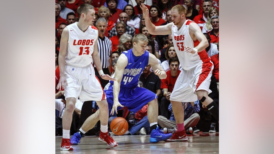 Air Force's Chase Kammerer (44) drives to the hoop guarded by New Mexico's Alex Kirk (53) and Cullen Neal (13) during the first half of an NCAA college basketball game at The Pit in Albuquerque, N.M., Wednesday, March 5, 2014. (AP Photo/Juan Antonio Labreche)