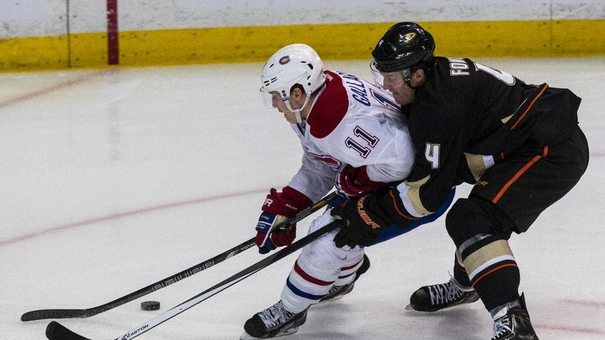Montreal Canadiens right wing Brendan Gallagher (11) and Anaheim Ducks defenseman Cam Fowler (4) vie for the puck during the first period of an NHL hockey game, Wednesday, March 5, 2014, in Anaheim, Calif.  (AP Photo/Ringo H.W. Chiu)