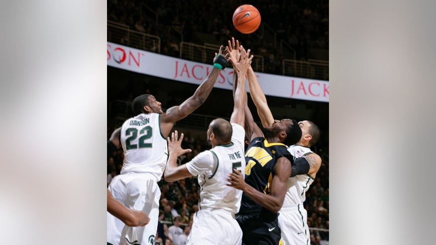Michigan State's Branden Dawson (22), Adreian Payne (5) and Denzel Valentine, right, and Iowa's Gabriel Olaseni (0) reach for a rebound during the first half of an NCAA college basketball game, Thursday, March 6, 2014, in East Lansing, Mich. (AP Photo/Al Goldis)