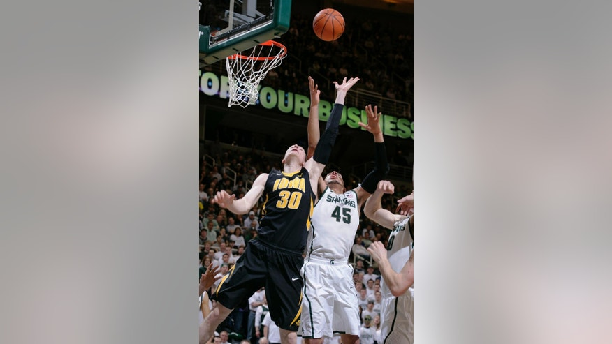 Iowa's Aaron White (30) and Michigan State's Denzel Valentine (45) reach for a rebound during the first half of an NCAA college basketball game, Thursday, March 6, 2014, in East Lansing, Mich. (AP Photo/Al Goldis)