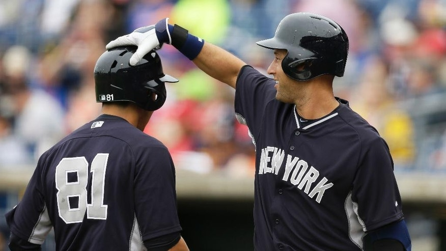 New York Yankees' Ramon Flores, left, celebrates with teammate Derek Jeter after hitting a home run during the third inning of an exhibition baseball game against the Philadelphia Phillies Thursday, March 6, 2014, in Clearwater, Fla. (AP Photo/Charlie Neibergall)
