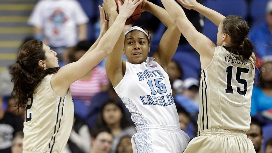 North Carolina's Allisha Gray, center, looks to pass as she is trapped by Wake Forest's Jill Brunori, left, and Millesa Calicott, right, during the first half of an NCAA college basketball game at the Atlantic Coast Conference tournament in Greensboro, N.C., Thursday, March 6, 2014. (AP Photo/Chuck Burton)
