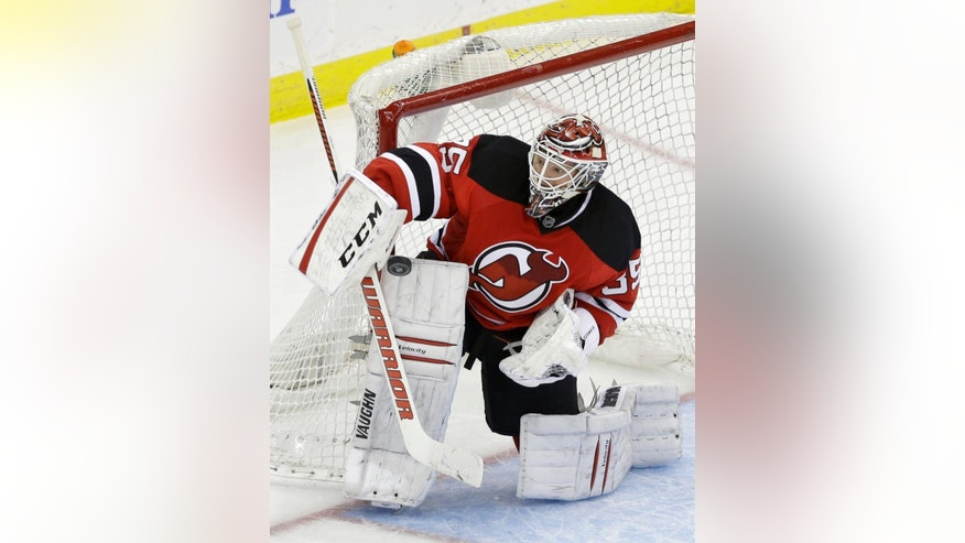 New Jersey Devils goalie Cory Schneider (35) makes a stick-save during the third period of an NHL hockey game against the San Jose Sharks, Sunday, March. 2, 2014, in Newark, N.J. The Sharks won 4-2. (AP Photo/Mel Evans)