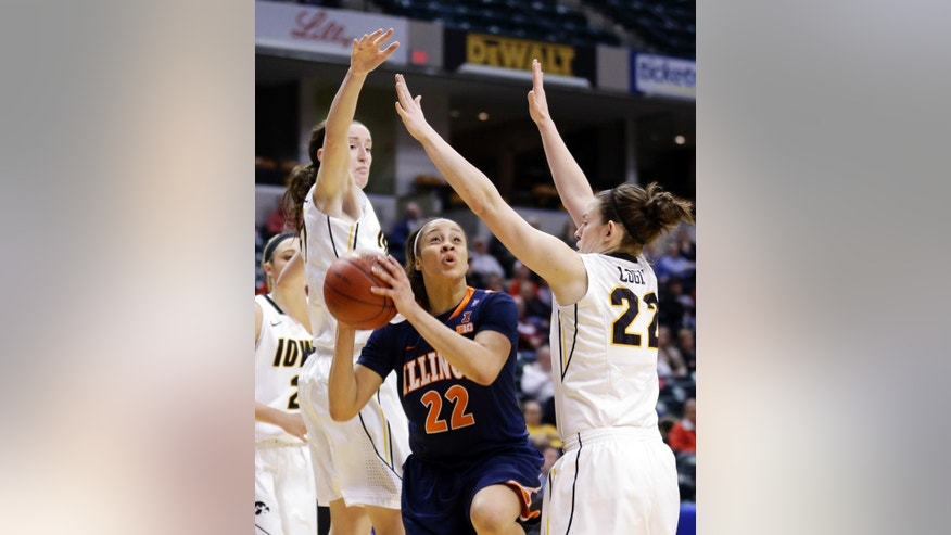 Illinois guard Ivory Crawford, center, shoots between Iowa guard Samantha Logic, right, and center Bethany Doolittle in the second half of an NCAA college basketball game in the opening round of the Big Ten Tournament in Indianapolis, Ind., Thursday, March 6, 2014. Iowa won 81-62. (AP Photo/Michael Conroy)