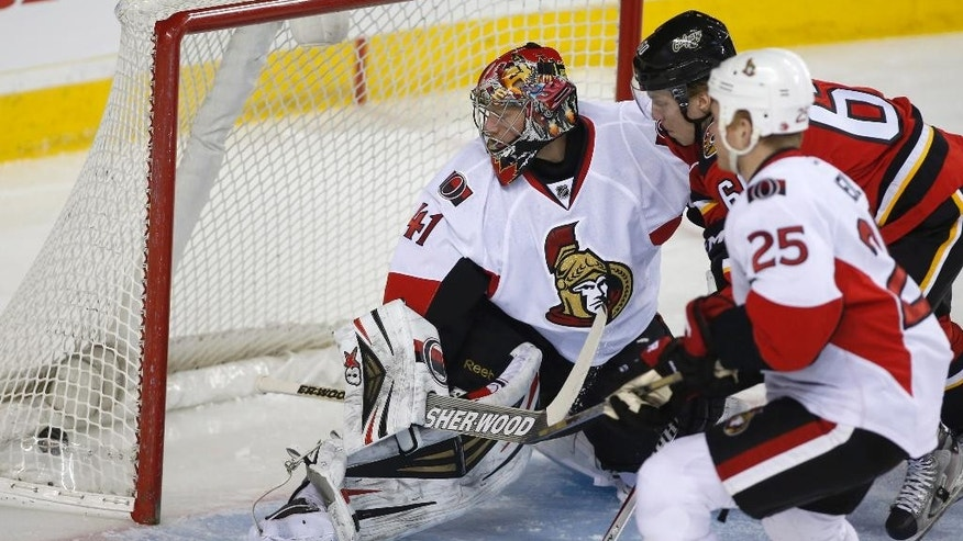 Ottawa Senators goalie Craig Anderson looks back at his net as Calgary Flames' Markus Granlund, of Finland, scores while Senators' Chris Neil (25) watches during the first period of an NHL hockey game Wednesday, March 5, 2014, in Calgary, Alberta. (AP Photo/The Canadian Press, Jeff McIntosh)