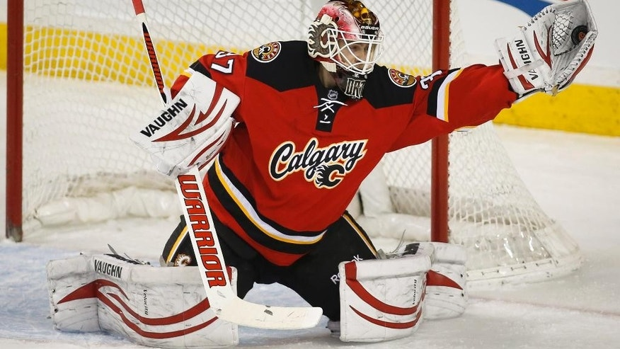 Calgary Flames goalie Joni Ortio, from Finland, makes a glove save during the first period of an NHL hockey game against the Ottawa Senators on Wednesday, March 5, 2014, in Calgary, Alberta. (AP Photo/The Canadian Press, Jeff McIntosh)