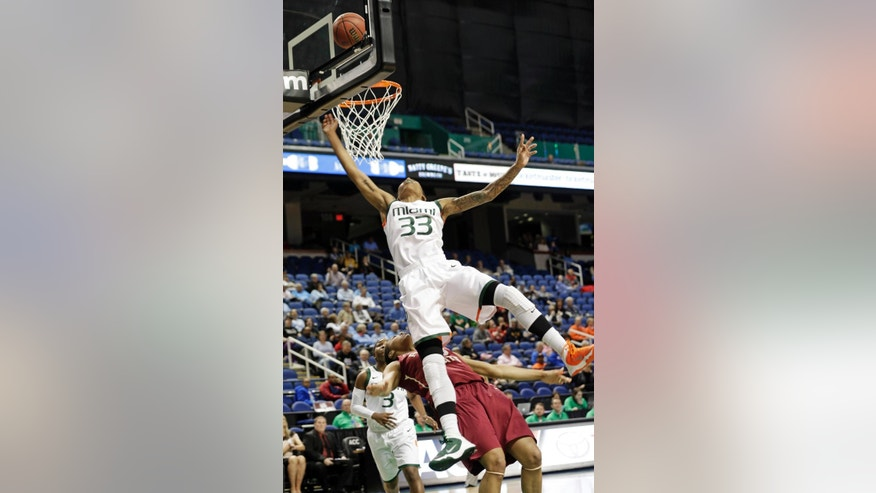 Miami's Suriya McGuire, top, falls over Miami's Suriya McGuire, bottom, during the first half of an NCAA college basketball game at the Atlantic Coast Conference tournament in Greensboro, N.C., Thursday, March 6, 2014. (AP Photo/Chuck Burton)