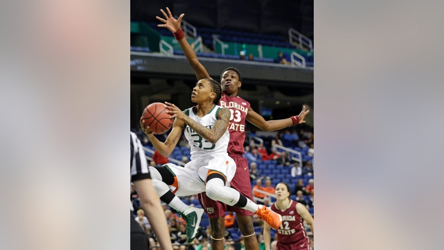 Miami's Suriya McGuire, left, drives past Florida State's Natasha Howard, right, during the first half of an NCAA college basketball game at the Atlantic Coast Conference tournament in Greensboro, N.C., Thursday, March 6, 2014. (AP Photo/Chuck Burton)