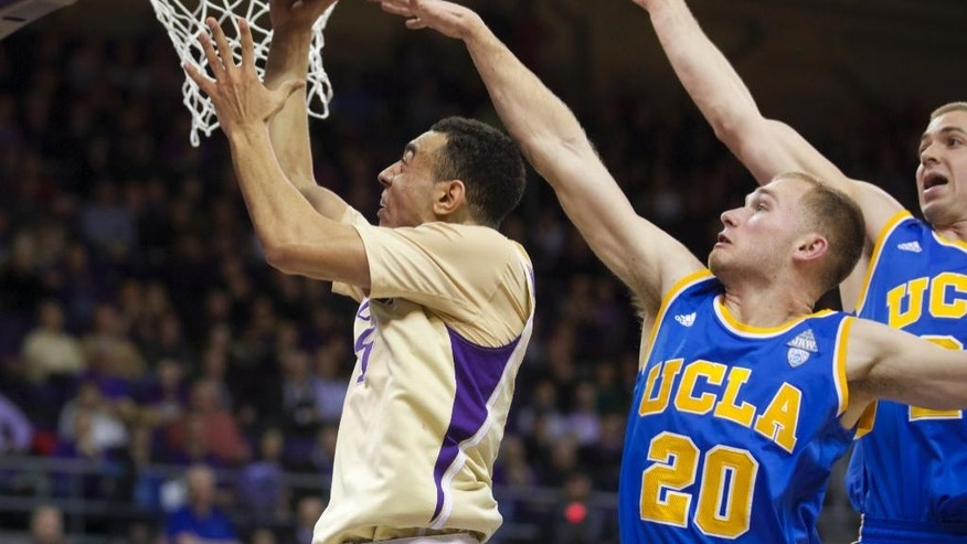 Washington's Nigel Williams-Goss, left, drives to the basket as UCLA's Bryce Alford defends in first half of an NCAA college basketball game on Thursday, March 6, 2014, in Seattle. (AP Photo/Stephen Brashear)