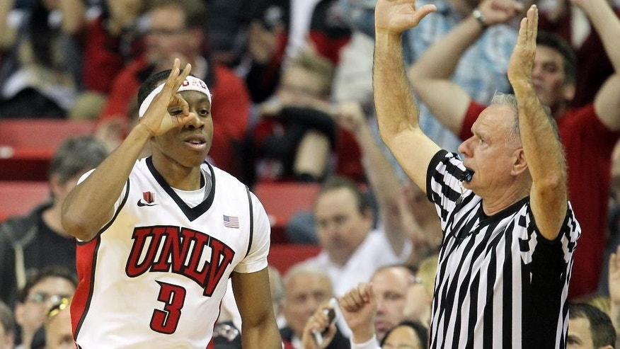 UNLV's Kevin Olekaibe, left, reacts after sinking a 3-point shot during the first half of an NCAA college basketball game against San Diego State on Wednesday, March 5, 2014, in Las Vegas. (AP Photo/Isaac Brekken)