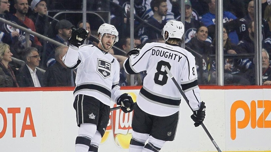 Los Angeles Kings' Mike Richards (10) and Drew Doughty (8) celebrate Richards' goal against the Winnipeg Jets during second-period NHL hockey game action in Winnipeg, Manitoba, Thursday, March 6, 2014. (AP Photo/The Canadian Press, John Woods)