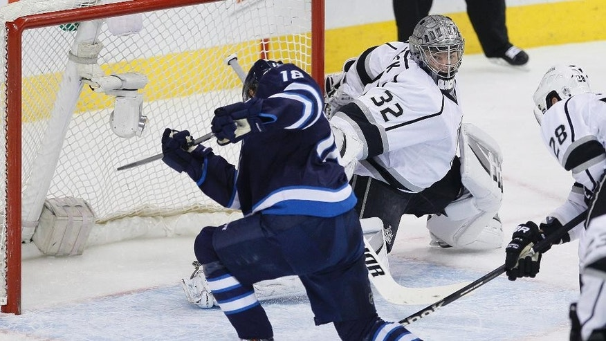 Winnipeg Jets' Bryan Little (18) fans on the open net shot against Los Angeles Kings goaltender Jonathan Quick (32) during first-period NHL hockey game action in Winnipeg, Manitoba, Thursday, March 6, 2014. (AP Photo/The Canadian Press, John Woods)