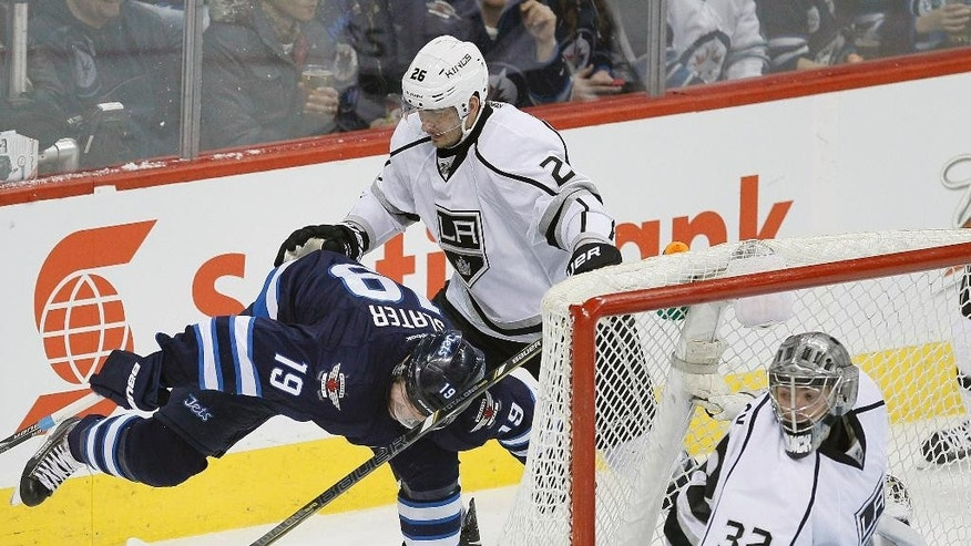 Los Angeles Kings' Slava Voynov (26) takes down Winnipeg Jets' Jim Slater (19) as Kings goaltender Jonathan Quick (32) looks on during first-period NHL hockey game action in Winnipeg, Manitoba, Thursday, March 6, 2014. (AP Photo/The Canadian Press, John Woods)