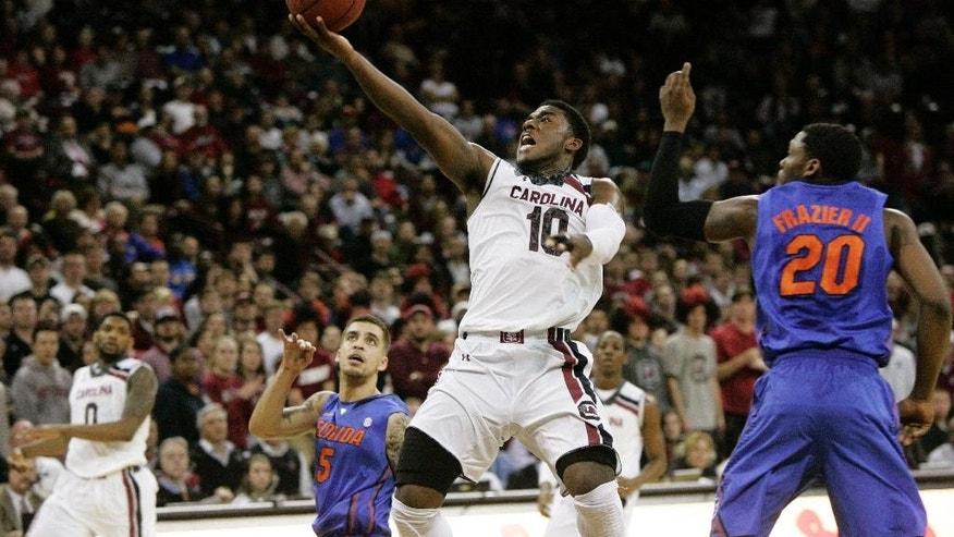 South Carolina's Duane Notice (10) goes up to the basket as Florida's Michael Frazier (20) tries to defend during the first half of their NCAA college basketball game Tuesday, March 4, 2014, in Columbia, S.C.(AP Photo/Mary Ann Chastain)