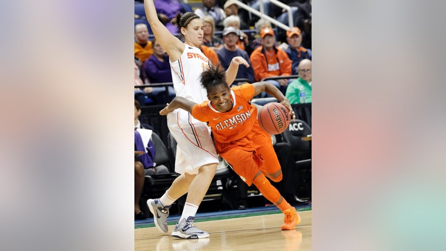 Clemson's Nikki Dixon, front, pushes around Syracuse's Brianna Butler, back, during the second half of an NCAA college basketball game at the Atlantic Coast Conference tournament in Greensboro, N.C., Thursday, March 6, 2014. Syracuse won 63-53. (AP Photo/Chuck Burton)